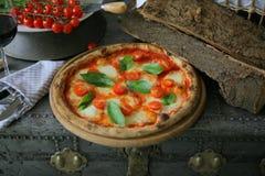 Neapolitanische Pizza mit Mozzarella, Kirschtomate und frischem Basilikum lizenzfreies stockbild