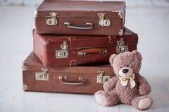 Near bunt för nallebjörn av tre bruna retro resväskor på det vita golvet arkivbilder