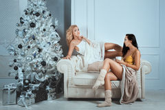 Near Christmas tree ornaments sit two girls and nice talk. Near the Christmas tree ornaments sit two girls and a nice talk. They are dressed for the home Royalty Free Stock Photos