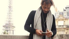 Near den manliga personen för mulatten som pratar med vänner vid smartphonen med hörlurar, Eiffeltorn lager videofilmer