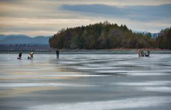 Men Ice Fishing on Lake Champlain in Late Afternoon. In the near distance, an outcropping of trees can be seen; the Adirondacks are in the far distance. The ice Royalty Free Stock Images