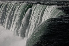 Near the Edge of Niagara Falls. This is a dramatic early mornign shot of the edge of Niagara Falls. This section is part of the famous Horseshoe Falls. Water in Stock Photo