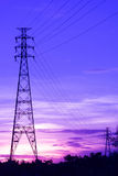 Near and Far High-Voltage towers Connected by Wires at Sunset Under Violet Sky. The Setting Sun Cast The Sky in Purple Color Stock Photography