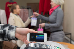 Near Field Communication - Man completing mobile Payment Woman shopping Stock Image