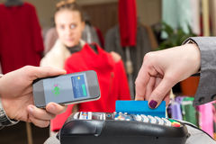 Near Field Communication - Man completing mobile Payment Woman shopping Royalty Free Stock Photography