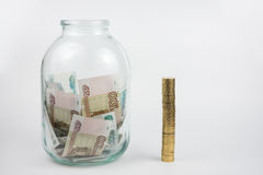 Near full of money is three-liter jar stack of coins. Near full of Russian money is three-liter jar stack of coins Stock Photos