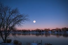 Near Full Moon Rising over Lake and Houses in Red and Blue Winte stock photos