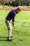 Near the golf hole. A golf player making a swing on a vibrant beautiful golf course Royalty Free Stock Image