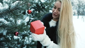 Near the green pine woman with long blond hair looks at the red box. On the tree hang Christmas decorations in mind the balls. The lady wants to know what`s stock video footage