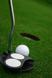 Near The Hole. Golf ball ready to hit by the putter to the hole Royalty Free Stock Image