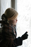 Near the icy window. A girl standing near the icy window Stock Photos