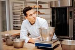 Baker wearing white uniform standing near kitchen scale. Near kitchen scale. Professional dark-haired baker wearing white uniform standing near kitchen scale royalty free stock photography