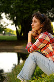 Near a lake. Young brunette is sitting near a lake Royalty Free Stock Photography