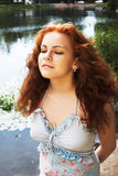 Near the lake. Close-up portrait of a beautiful red-headed girl posing near the lake stock photo