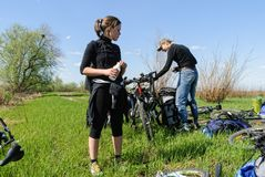 Group of cycle tourists stopped for rest in field Stock Image