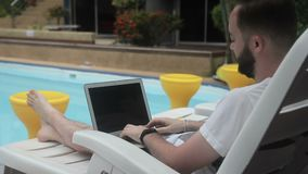 Near pool bearded man on deckchair quickly typing text on the laptop. During busy vacation businessman prints a post in social networks with a recall of living stock video