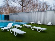 Near the pool with hot thermal water there are white plastic chaise lounges. White plastic chaise lounges near the pool with hot thermal water on a green stock images