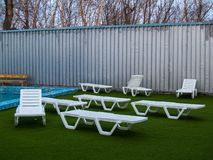 White plastic chaise lounges stand near the pool with hot thermal water. Near the pool with hot thermal water there are white plastic chaise lounges on a green royalty free stock photography