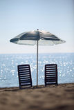 Near sea ashore two chairs stay under umbrella Royalty Free Stock Images