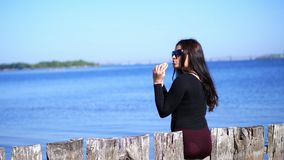 Summer, near sea beach. woman, with long dark hair, wearing sunglasses, with apetite eating fastfood, hamburger.former. Near sea beach. woman, with long dark stock video