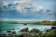 Near the sea coast, house near the sea, stones in the water Royalty Free Stock Images