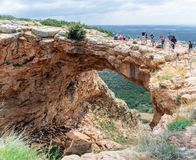 Tourists stand and look at the Keshet Cave - ancient natural limestone arch spanning the remains of a shallow cave with sweeping v. Near Shlomi, Israel, March 31 Royalty Free Stock Photo