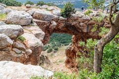 Tourists stand and look at the Keshet Cave - ancient natural limestone arch spanning the remains of a shallow cave with sweeping v. Near Shlomi, Israel, March 31 Stock Photos
