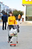 Near the shop. Girl with shopping trolley going from shop to car Royalty Free Stock Photography