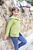 Near the stone wall beautiful girl. The little girl is standing by the stone wall Royalty Free Stock Photo