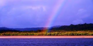 Near vatten för genomskinlig vibrerande regnbåge Arkivfoto