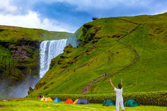 Near a waterfall put some tourist tents. Grand waterfall Skogafoss. Near a waterfall put some colorful tourist tents. Elderly woman shocked by the beauty of the Royalty Free Stock Images