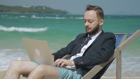 Near waves of ocean businessman is working behind a laptop in a suit. Unshaven male person sitting in an armchair in shorts and a business tie and typing text stock video footage