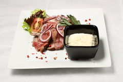 Nearly fresh sliced meat with horseradish. Beef steak with red pepper and black bowl with white sauce Stock Image