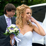 Nearly Limousine. Near the white limo are the bride and groom, the wind is waving her hair and veil Stock Photos