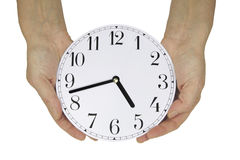 Nearly time to go home. Emale hands holding a clock face showing seventeen minutes to five, which is almost home time for many workers, isolated on a white Royalty Free Stock Photo