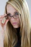 Nearsighted Schönheit schaut über ihren Gläsern Stockbilder