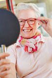 Nearsighted senior woman with new Royalty Free Stock Image