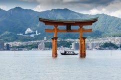 NearTorii turístico do barco - porta de flutuação da ilha de Miyajima (Itsukushima) fotografia de stock royalty free