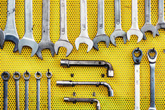Neat arrangement of tools on yellow pegboard Stock Photos