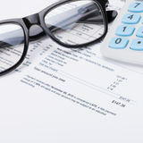 Neat calculator with pen, glasses and utility bill under it - close up shot Royalty Free Stock Image