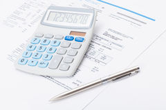 Neat calculator with silver pen and utility bill under it Royalty Free Stock Image