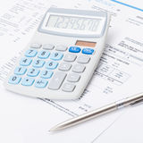 Neat calculator with silver pen and utility bill under it - close up shot Stock Photos