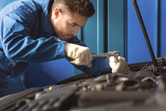 Neat careful mechanic using special wrench Royalty Free Stock Photo
