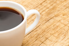 Neat cup of black coffee on old wooden table Royalty Free Stock Image