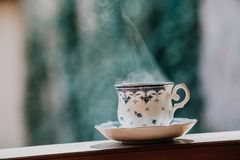 Elegant tea cup and stand shelf. Neat cup for tea with blue pattern and a saucer stand on wooden rails in a blurred background Royalty Free Stock Photos