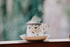 Elegant tea cup and stand shelf. Neat cup for tea with blue pattern and a saucer stand on wooden rails in a blurred background Royalty Free Stock Photo