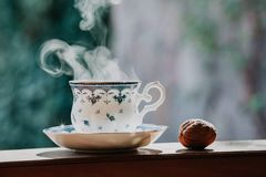 Elegant tea cup and walnut on shelf. Neat cup for tea with a blue pattern and a saucer stand on wooden rails on a blurred background. Nearby is a walnut Royalty Free Stock Images