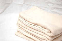 Neat diapers. A stack of unbleached cotton diapers folded neatly on a white sheet Stock Photos