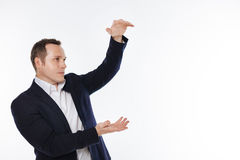 Neat engaged gentleman holding some object in his hands Royalty Free Stock Images