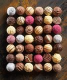 Neat flat lay of luxury chocolate pralines. Or bonbons arranged in a rectangle in rows displaying a wide selection of decorative patterns and textures on rustic royalty free stock images